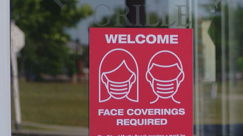 A mask required sign still hangs outside a restaurant in Myrtle Beach.