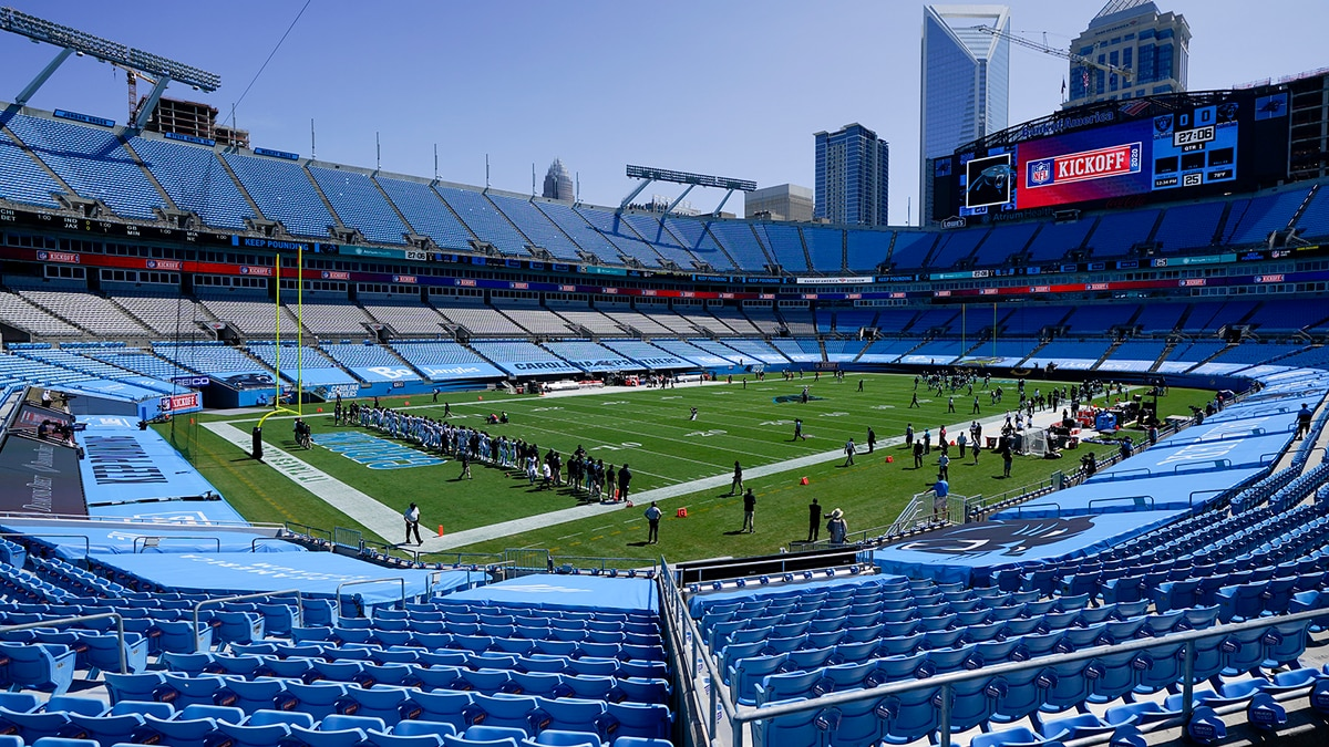 Members of the Carolina Panthers stand during a special presentation in an empty stadium before...