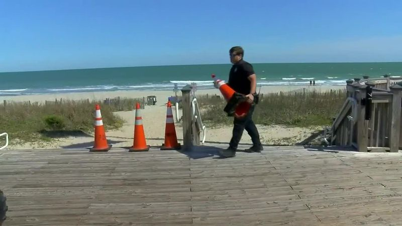 Myrtle Beach police officer removes barriers from public beach access.