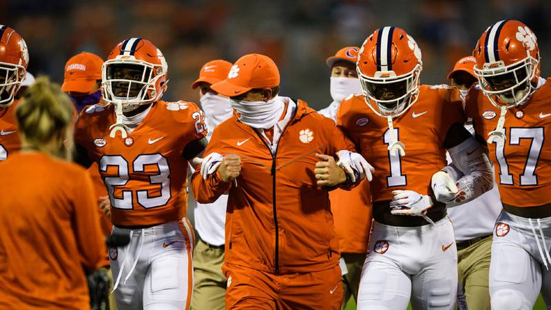 """Dabo Swinney is joined arm in arm with players during Clemson's """"Victory Walk"""" ahead of their..."""