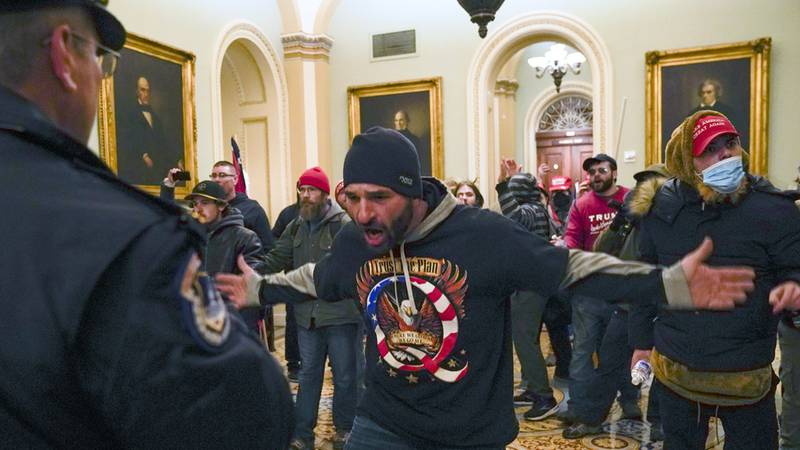 Trump supporters gesture to U.S. Capitol Police in the hallway outside of the Senate chamber at...