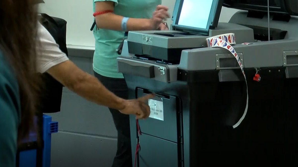 A voter pushes their ballot into the emergency bin on a broken scanner.