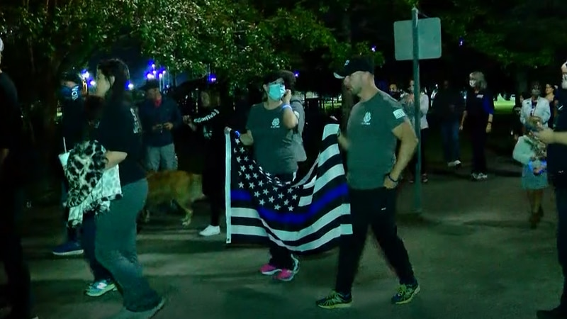 Families of law enforcement led a mile-long walk around the Market Common pond Monday night, to...