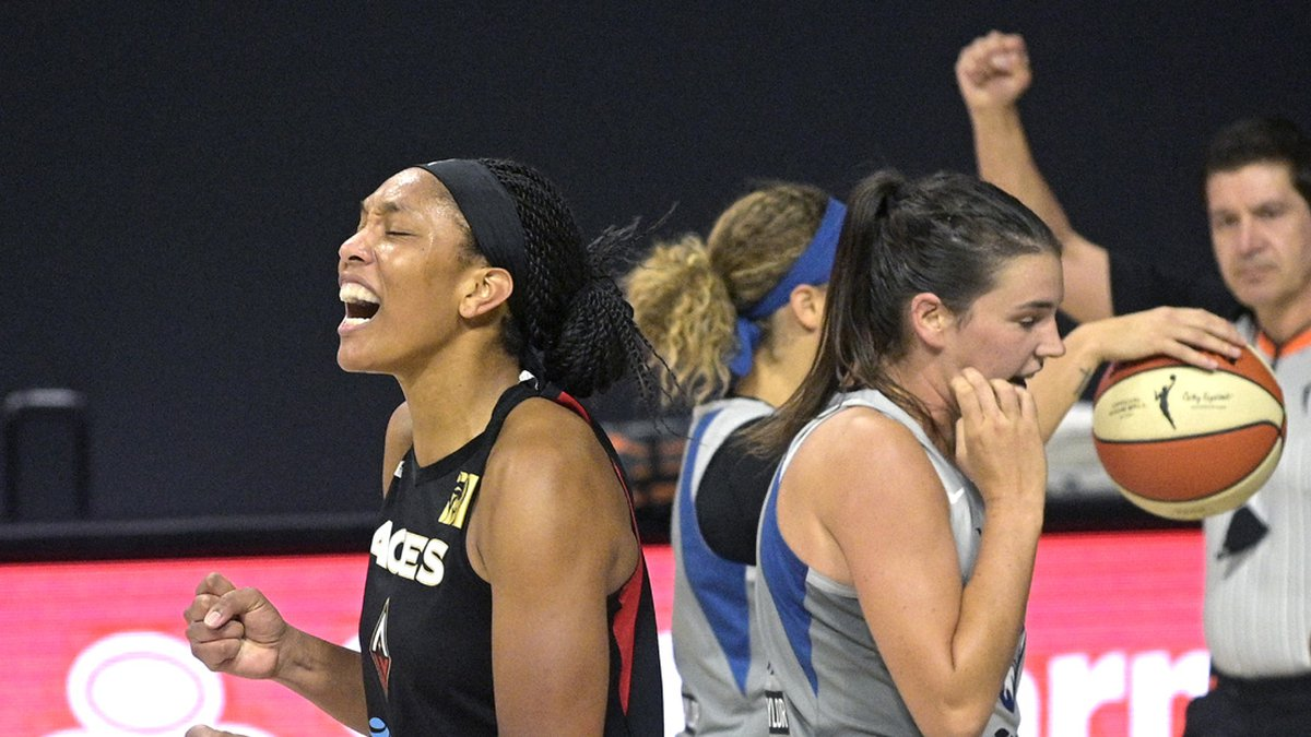 Las Vegas Aces center A'ja Wilson, left, reacts behind Minnesota Lynx guard Bridget Carleton...