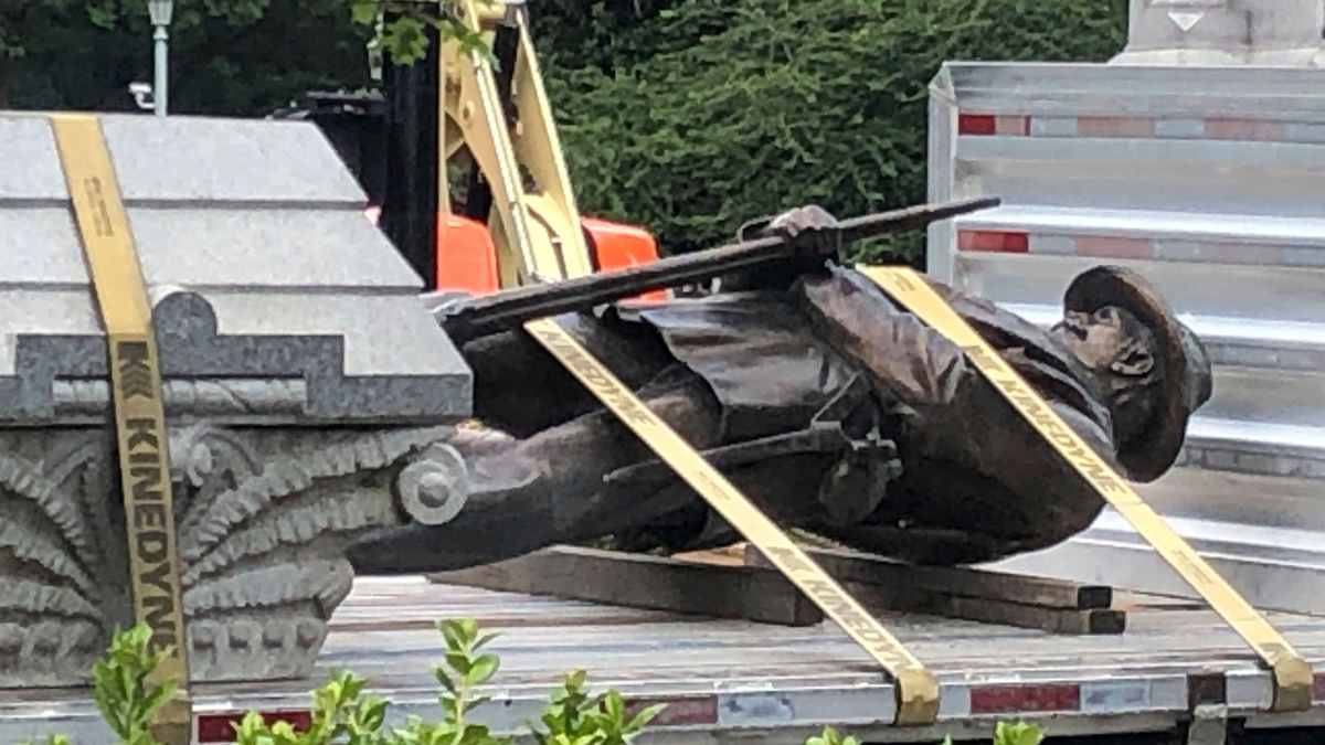 The statue of a Confederate soldier and plinth sit on a flatbed truck at the Old Capitol in...