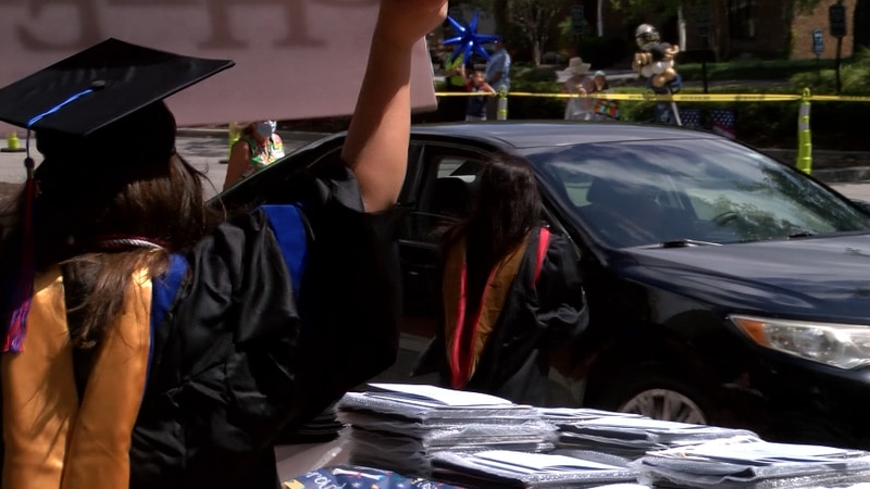 Today, instead of walking across the stage, graduates drove across the parking lot to get their...