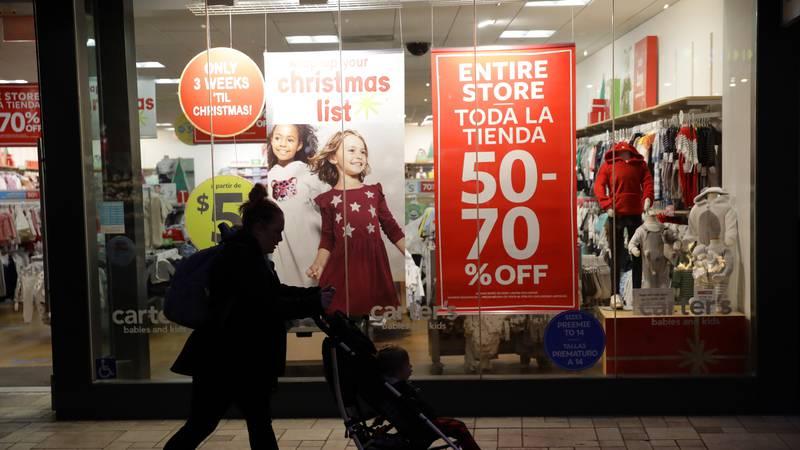 A shopper walks in front of Christmas sales signs Monday, Dec. 16, 2019, in Santa Clarita,...