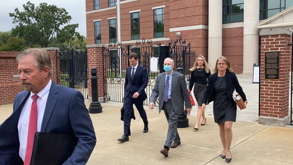 Former SCANA CEO Kevin Marsh, center, walks out of a courtroom with his lawyers after being...