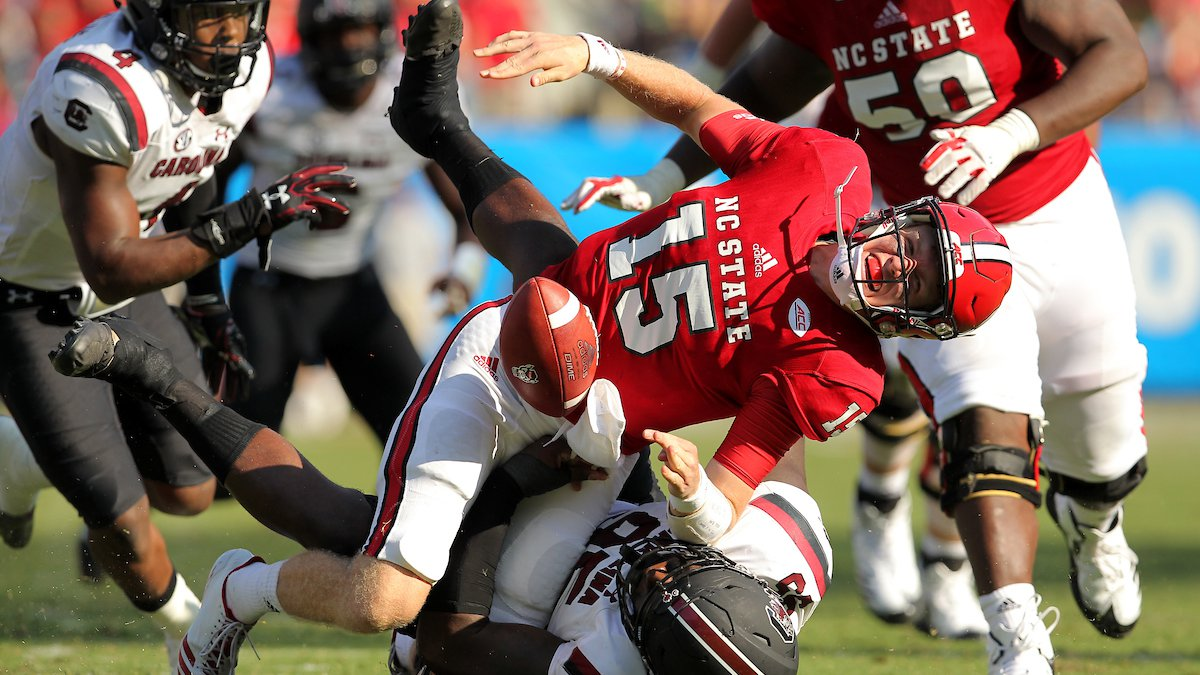 N.C. State quarterback Ryan Finley loses the ball as he is sacked by South Carolina's Dante...