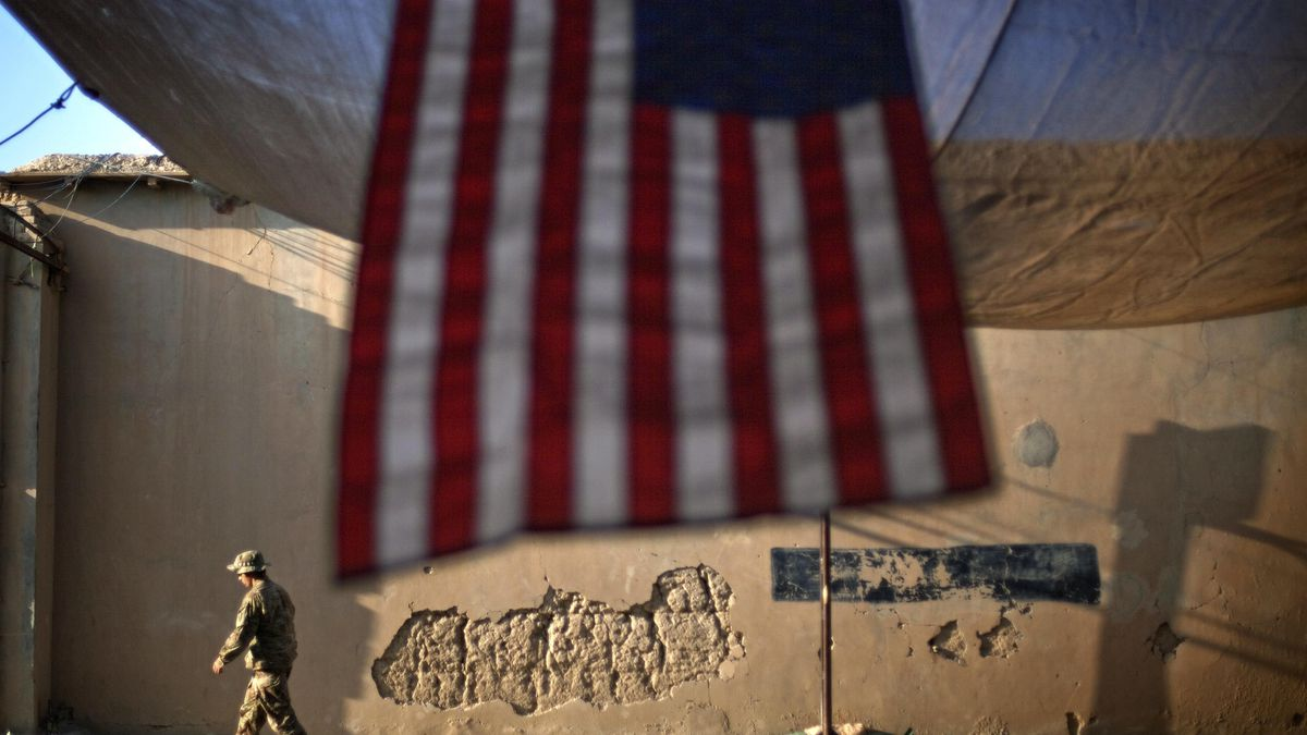 FILE - In this Sept. 11, 2011 file photo, a U.S. Army soldier walks past an American Flag...