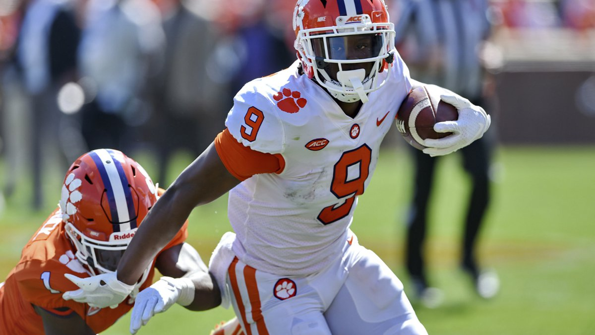 Clemson's Travis Etienne (9) rushes out of the tackle attempt by Derion Kendrick during...