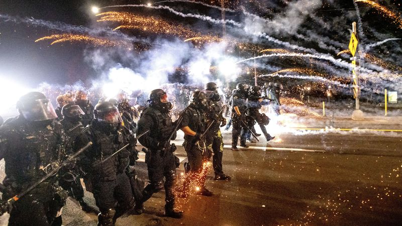 FILE - In this Sept. 5, 2020 file photo, police use chemical irritants and crowd control...