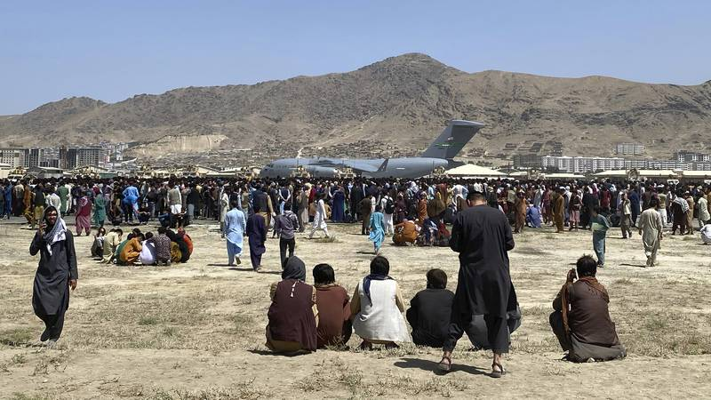 FILE - In this Aug. 16, 2021 file photo, hundreds of people gather near a U.S. Air Force C-17...