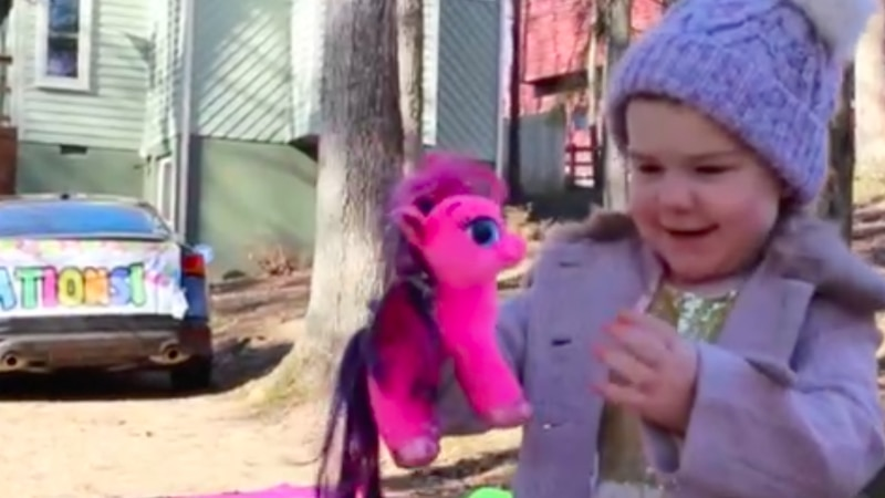 Charlie Blocks holds a toy unicorn during a car parade honoring the end of her cancer treatments.