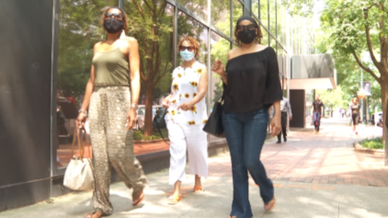 Women wear masks as they walk down the streets of downtown Columbia.